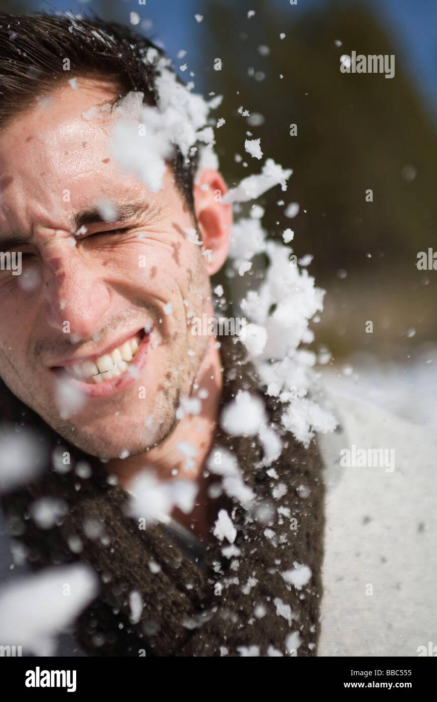 Mann im Gesicht von Schneeball getroffen Stockbild