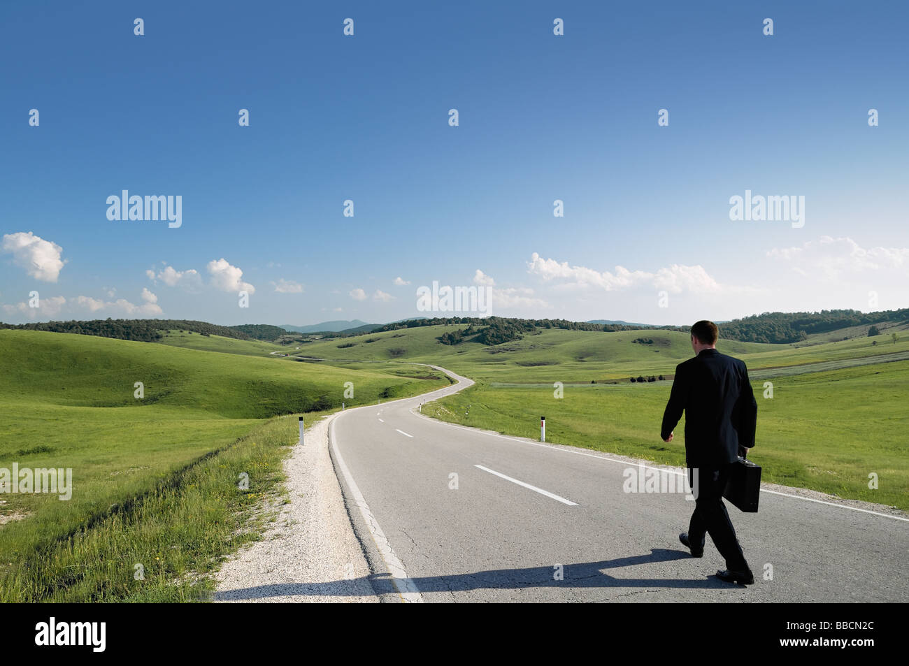 Geschäftsmann zu Fuß entlang einer abgelegenen Landstraße Rückansicht Stockbild