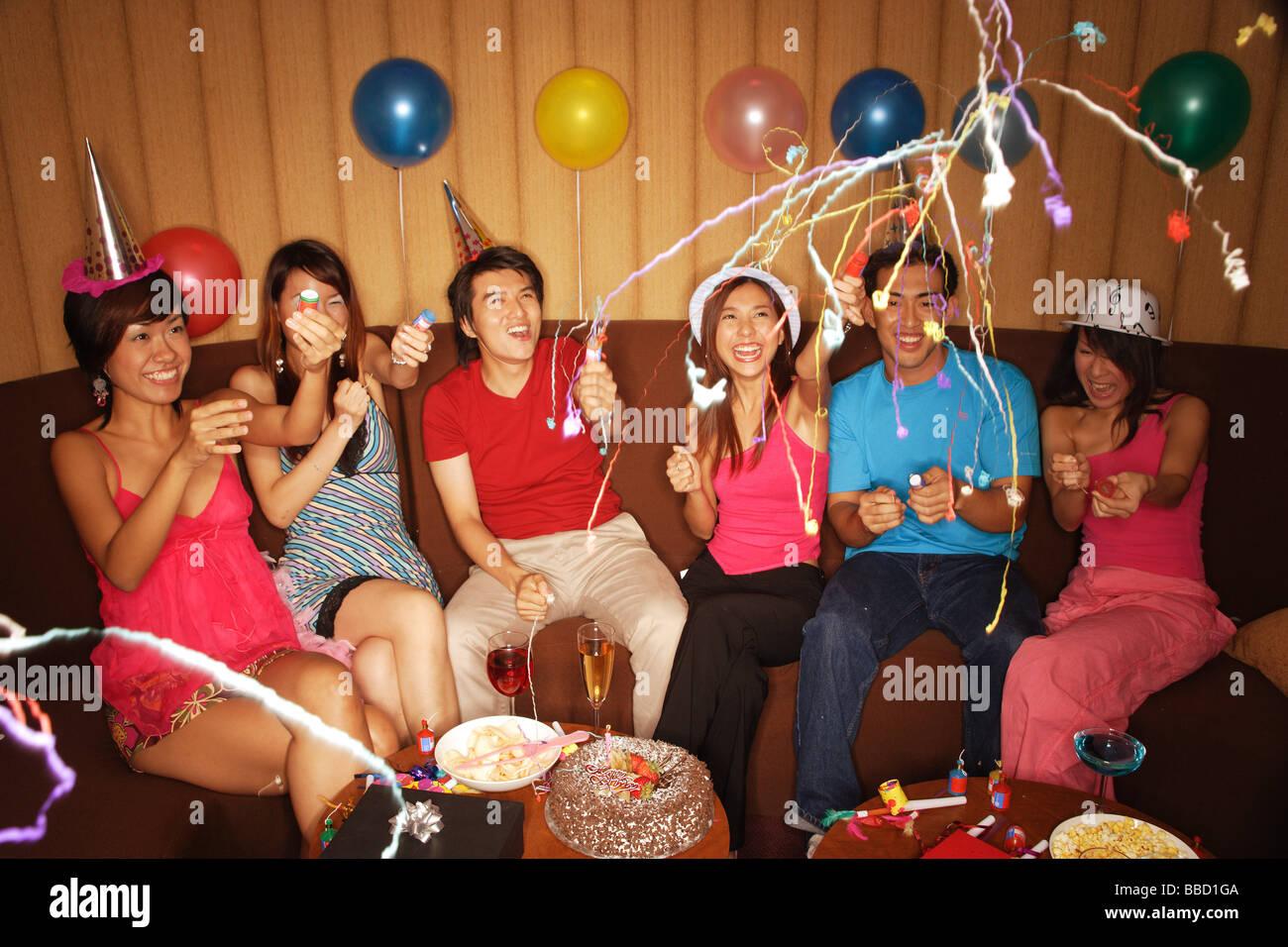 Jugendliche Feiern Mit Crackern Partyhute Und Luftballons Stockbild