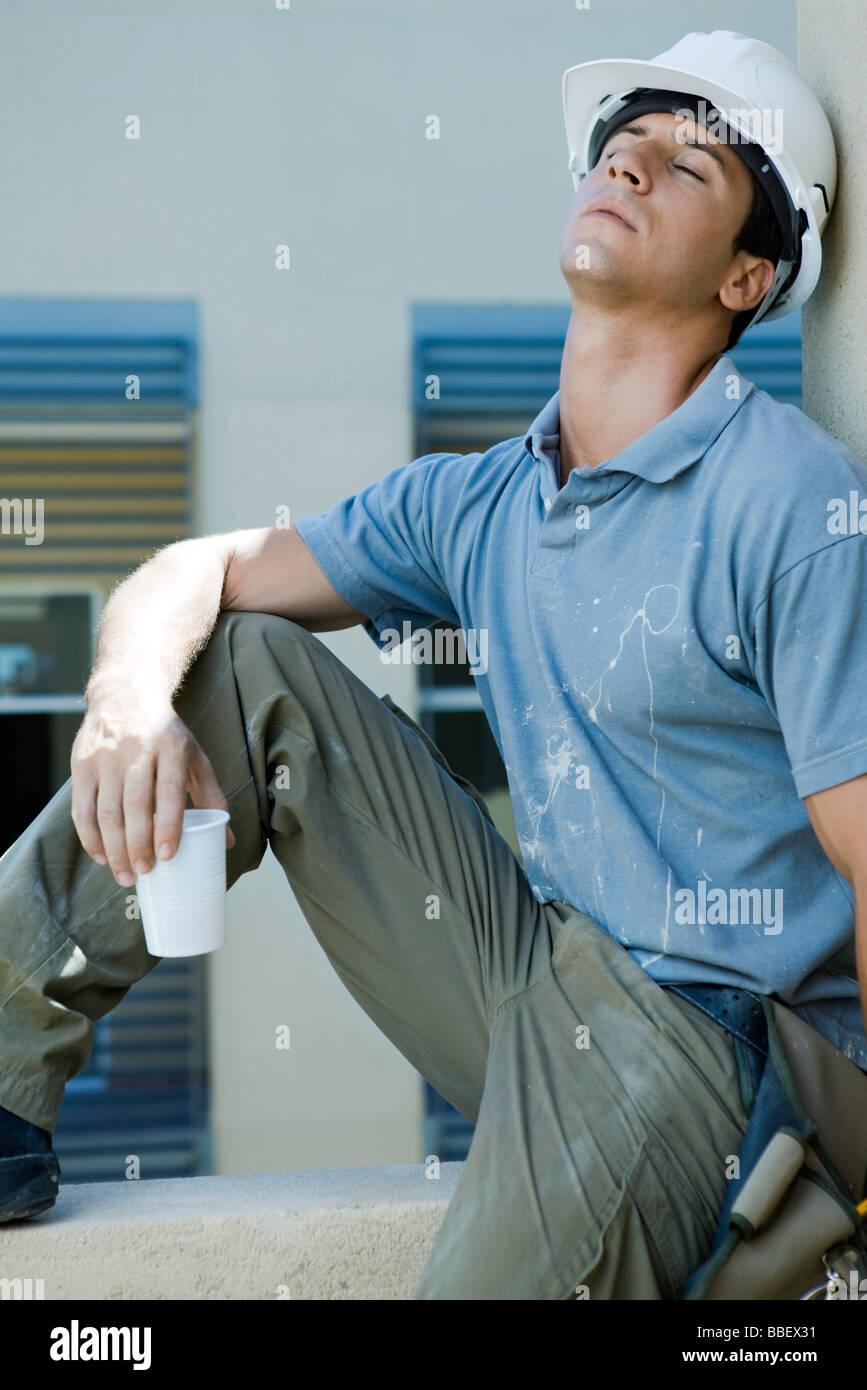 Bauarbeiter sitzen auf Sims, schiefen Kopf nach hinten, Augen geschlossen, Pause Stockbild