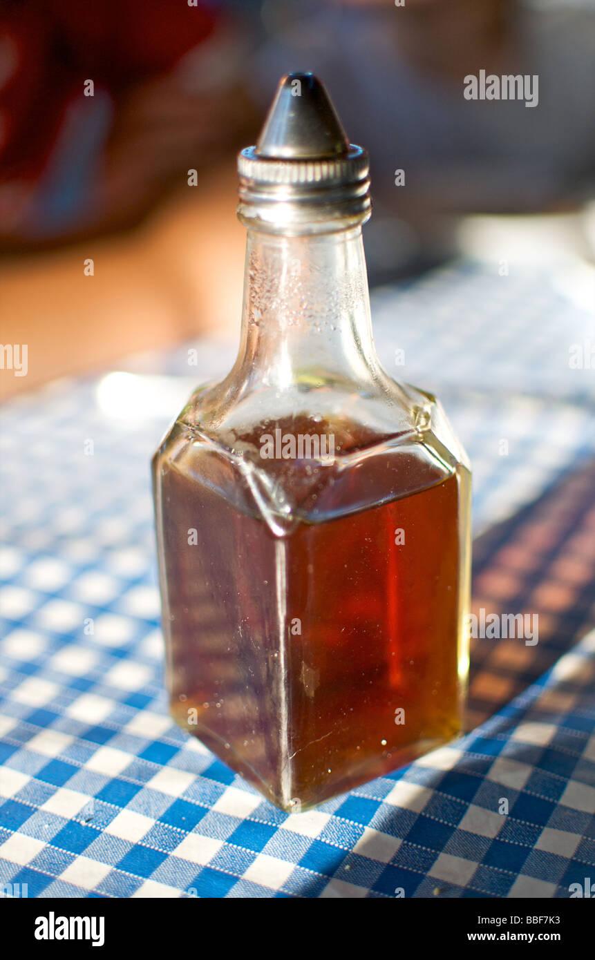 Eine Flasche Essig stand auf einer blau-weißen Tischdecke in einem café Stockbild