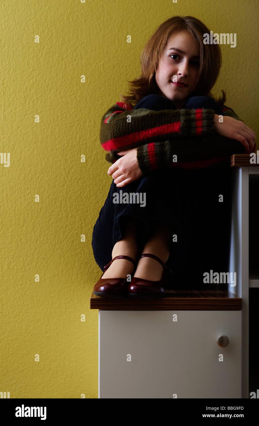 Junges Mädchen sitzt auf einem Schritt Stockbild