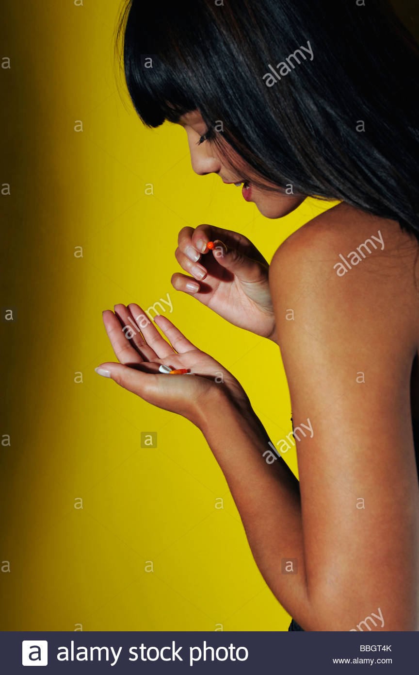 Junge Frau, die Einnahme von Pillen, Studio gedreht Stockbild