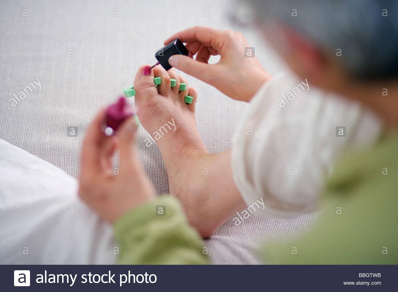 Ältere Frau geben sich bei Pediküre zu Hause Stockfoto