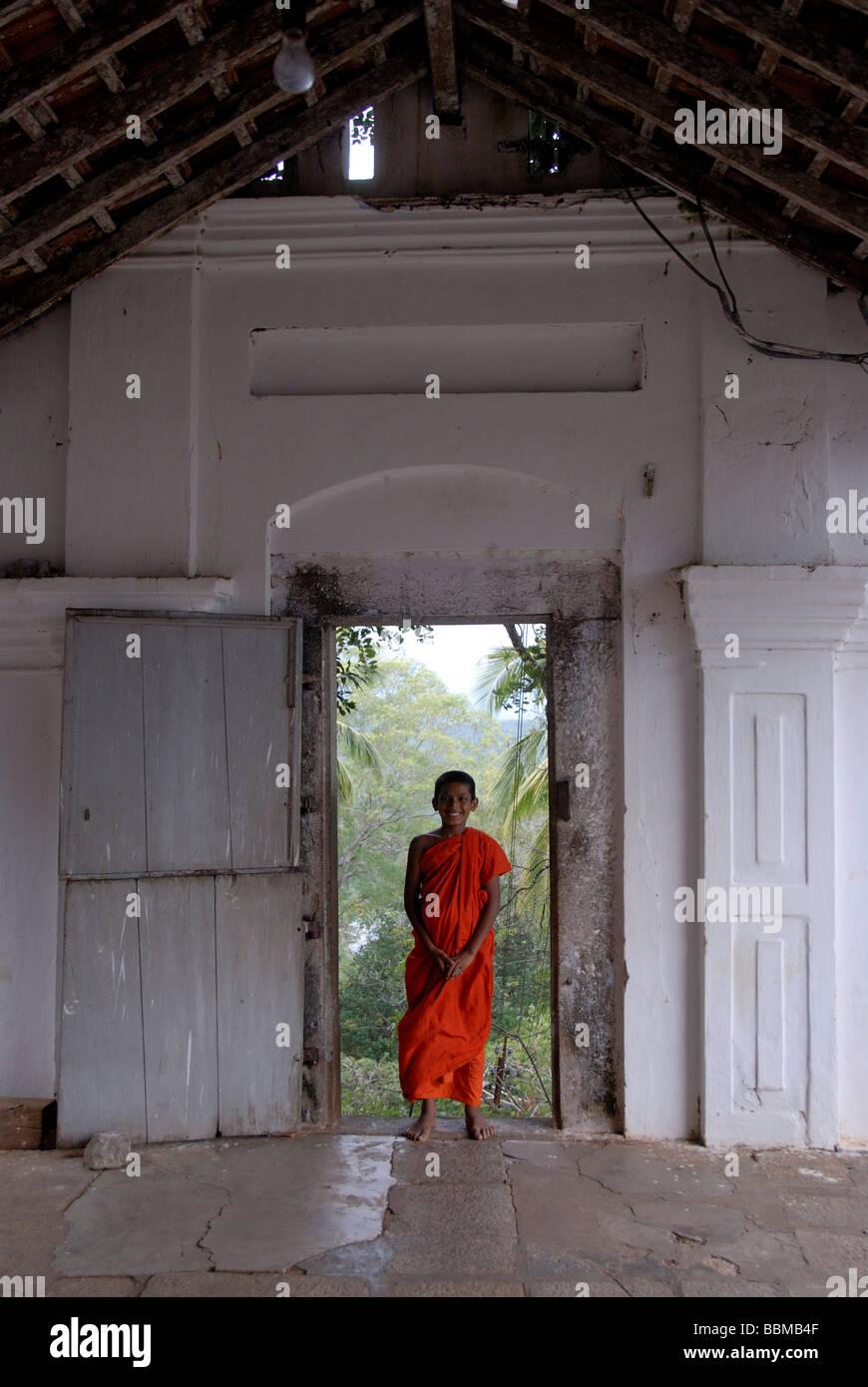 Buddhismus, ein Neuling in einem roten Gewand steht im Eingangsbereich, Mulgirigala Tempel, Mulkirigala Vihara, Stockbild