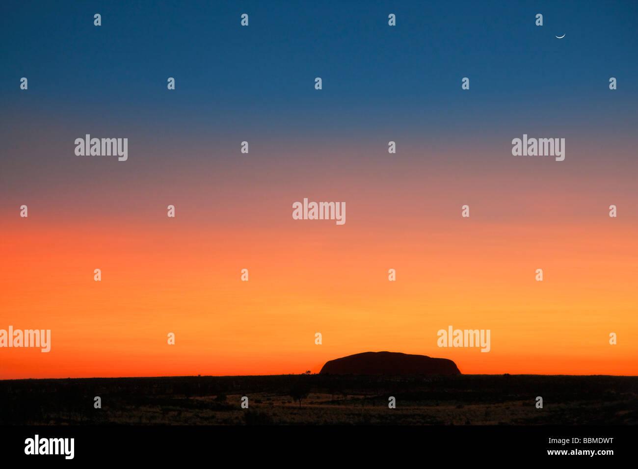 Australien, Northern Territory. Vor Sonnenaufgang ist Uluru oder Ayers Rock vor einem herrlichen Blut roten oder Stockbild