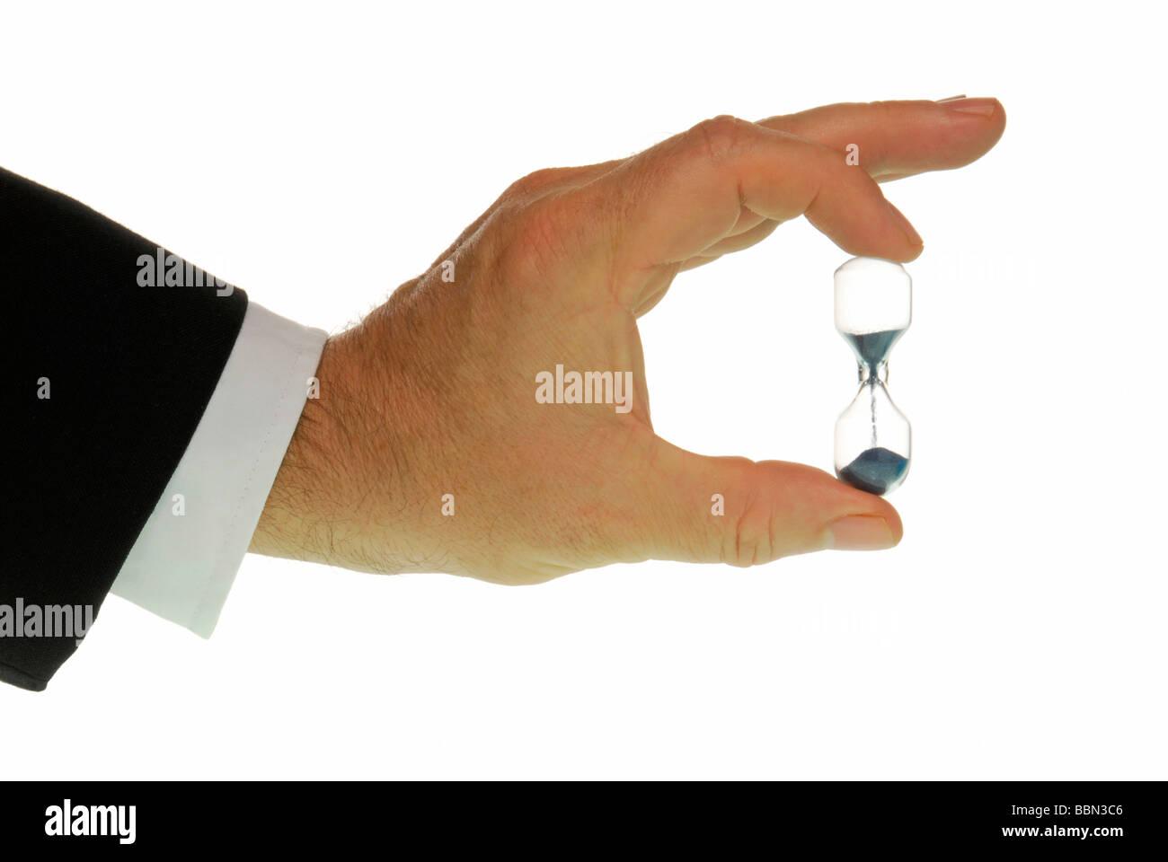 Manager-Hand mit Sanduhr, symbolisches Bild für Zeitdruck Stockbild