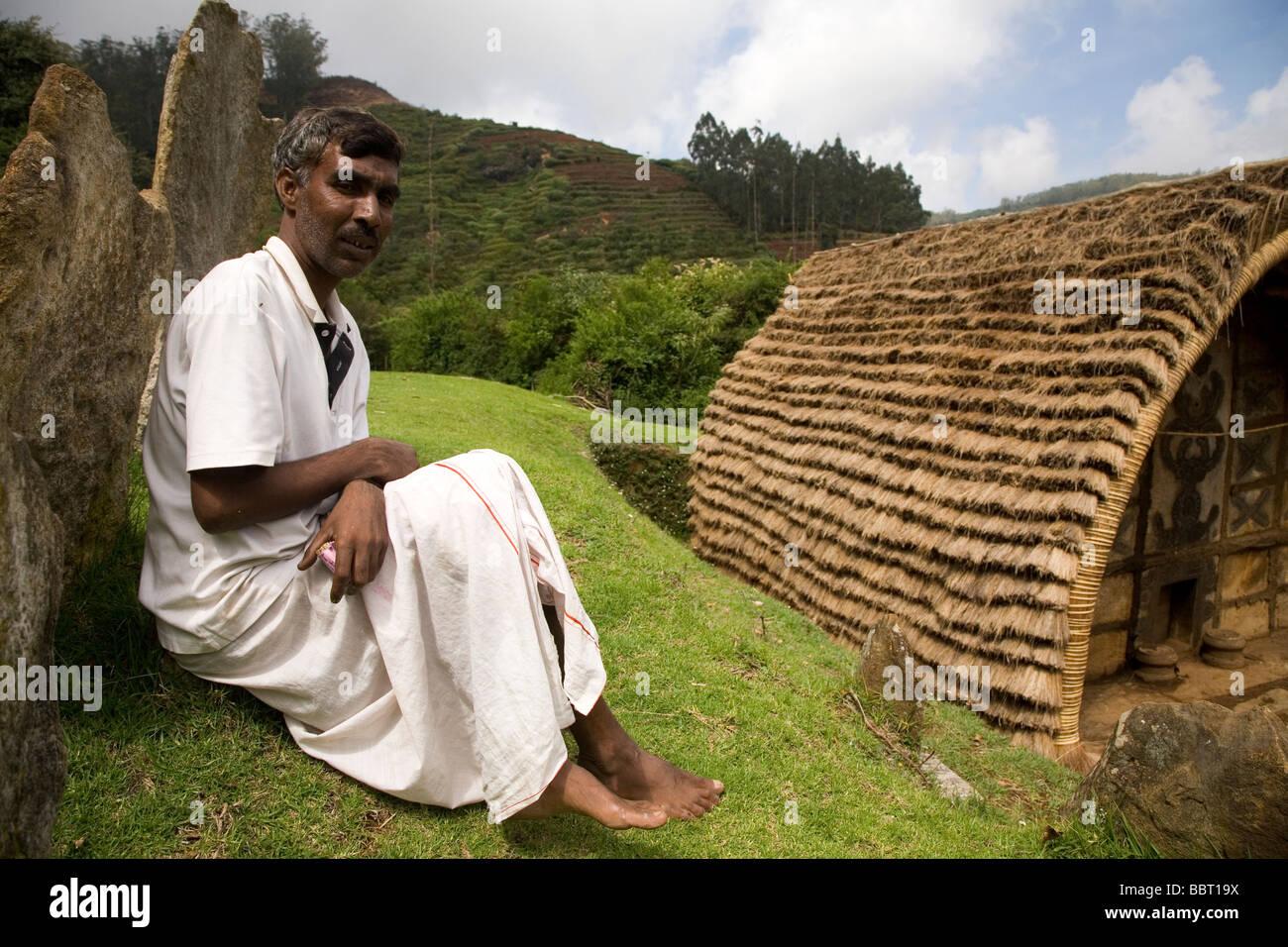 Ein Mann sitzt durch einen Tempel in einem Toda Stammes-Munder (Siedlung). Der Mund ist innerhalb des Botanischen Stockbild