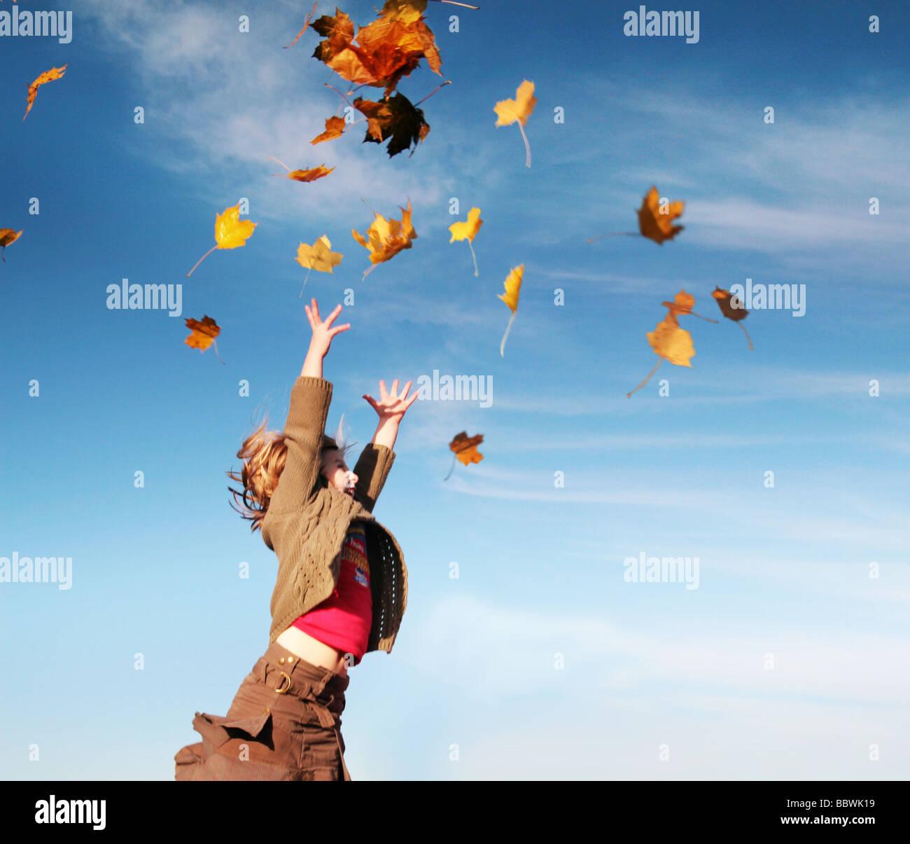 Mädchen fangen Blätter im Herbst Stockbild