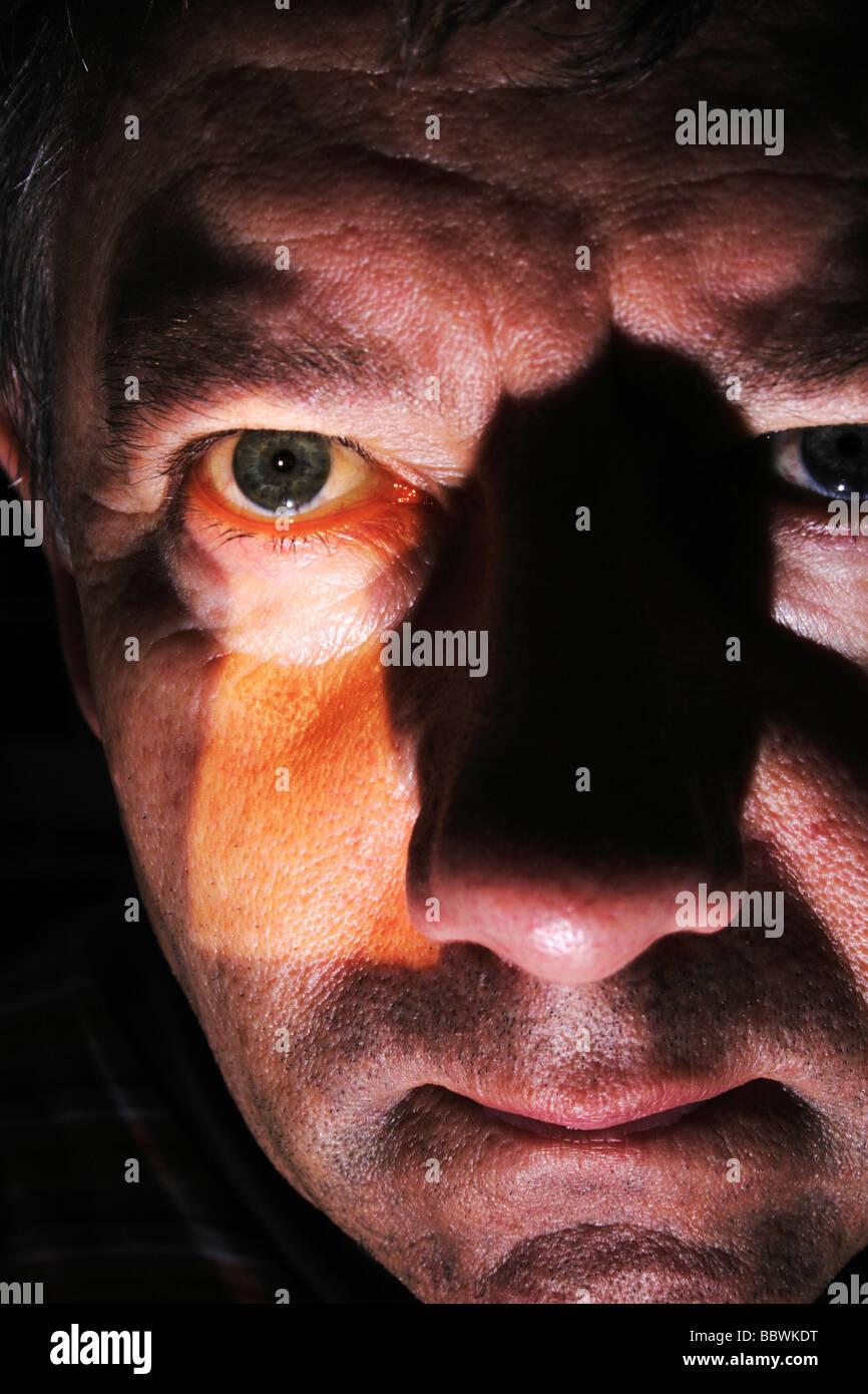 Ein Mann starrte durch ein Schlüsselloch mit Schlüsselloch Bild auf seinem Gesicht. Stockbild