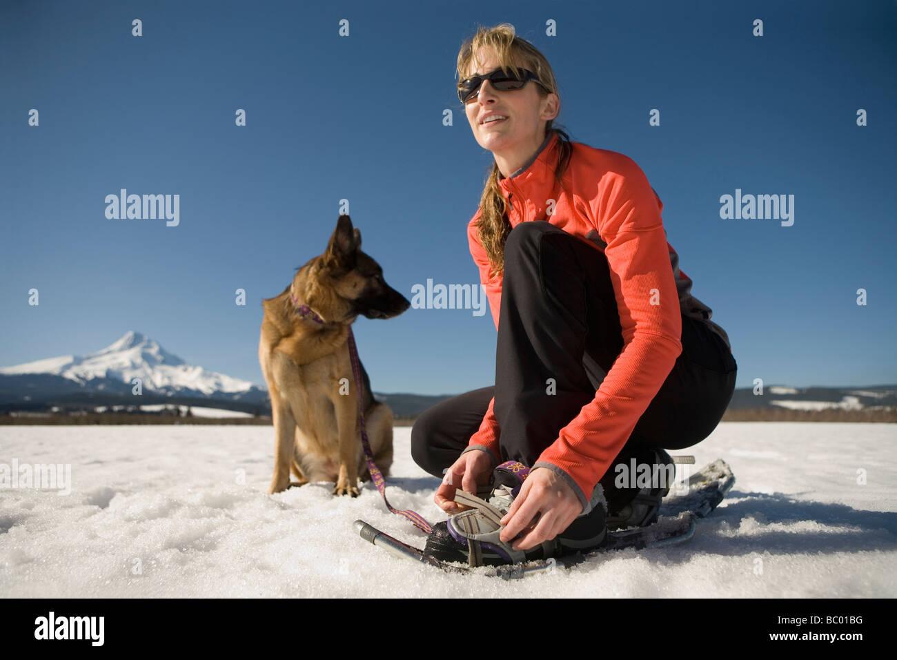 Junge Frau mit Hund legt auf Schneeschuhen in der Nähe von Mount Hood, Oregon. Stockbild