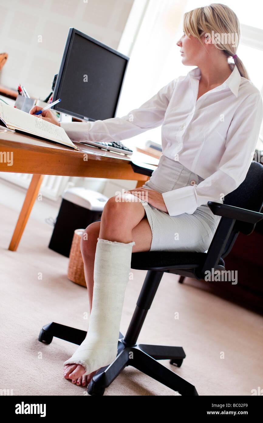 Frau bei der Arbeit mit Gipsverband am Bein Stockbild