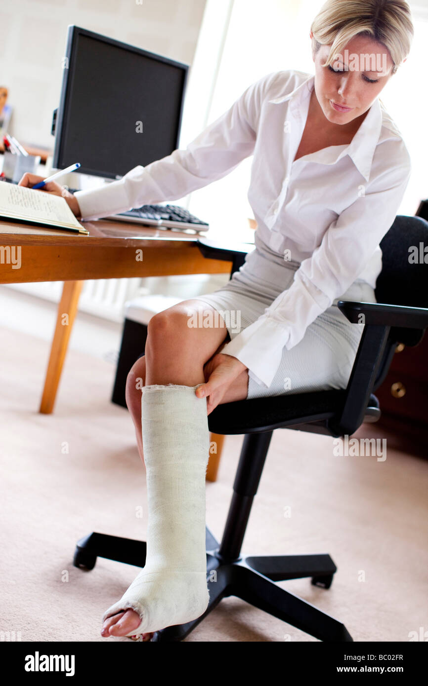 Frau im Büro mit Gipsverband Stockbild