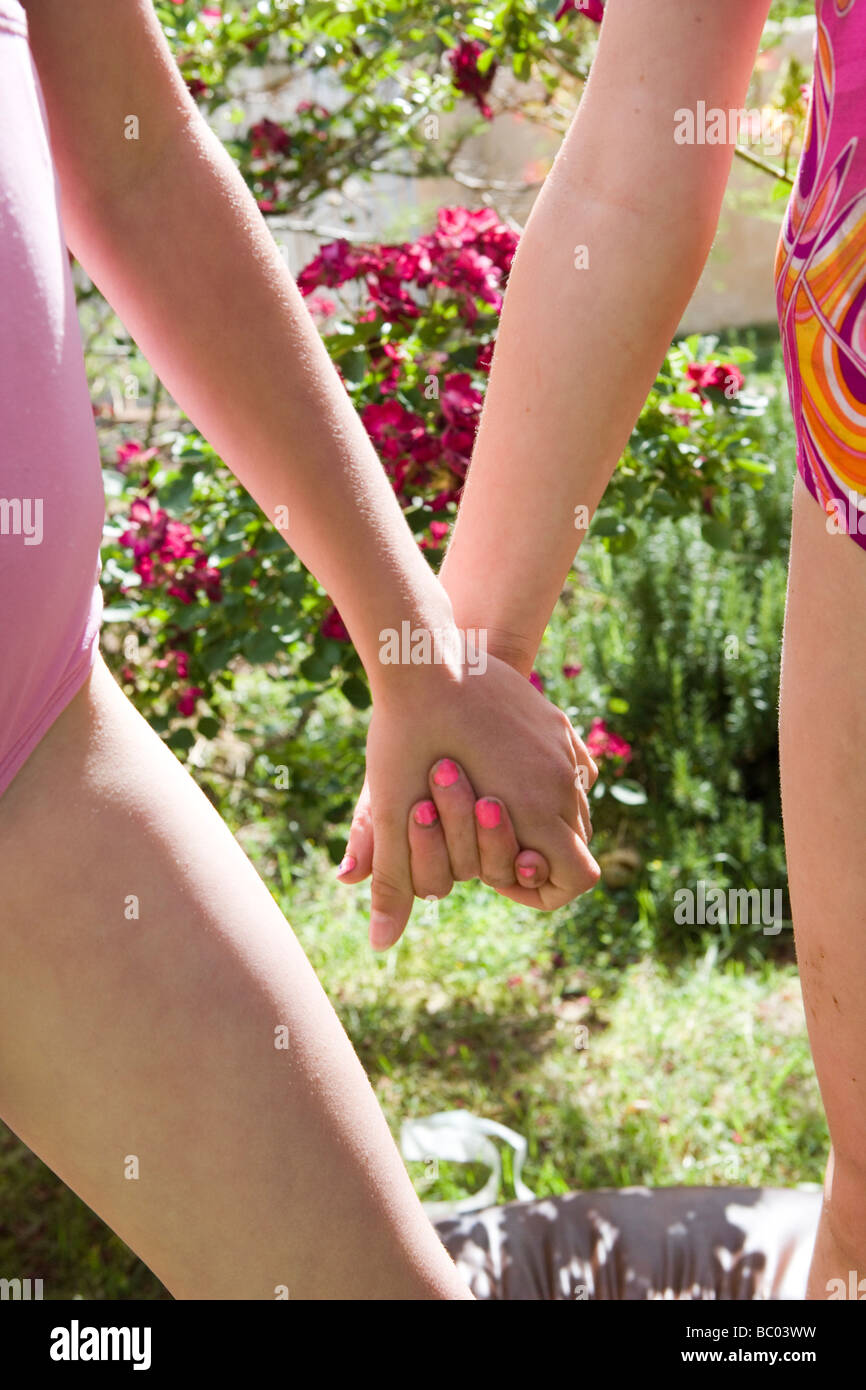 zwei siebenjährige Mädchen Hand in Hand im Freien, zwei bestfriends Stockbild