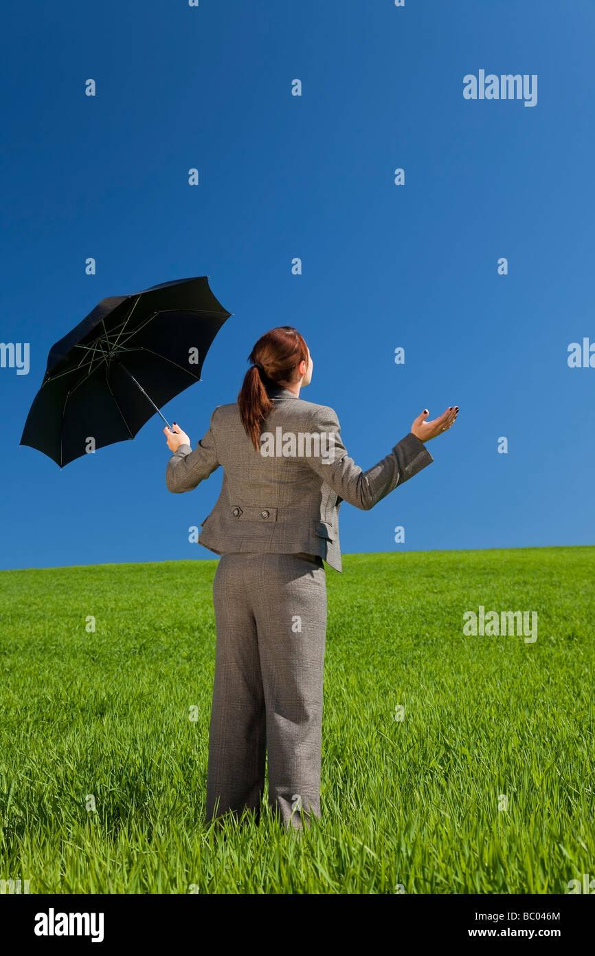 Konzept-Schuss einer jungen Frau in einem grünen Feld unter einem strahlend blauen Himmel halten und Sonnenschirm Stockfoto