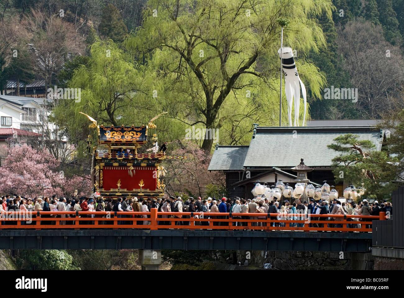 Ein traditionelle Schwimmer hält auf der Nakabashi-Brücke während des Frühlingsfestes Takayama Stockbild