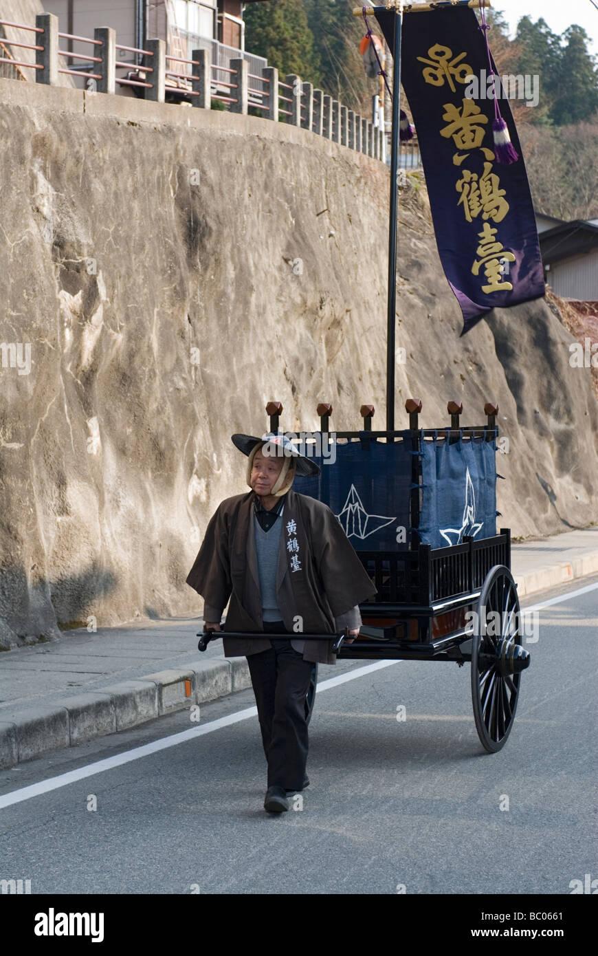 Ein Mann mit Festival Kleidung zieht einen traditionellen Karren mit Banner während des Frühlingsfestes Stockbild