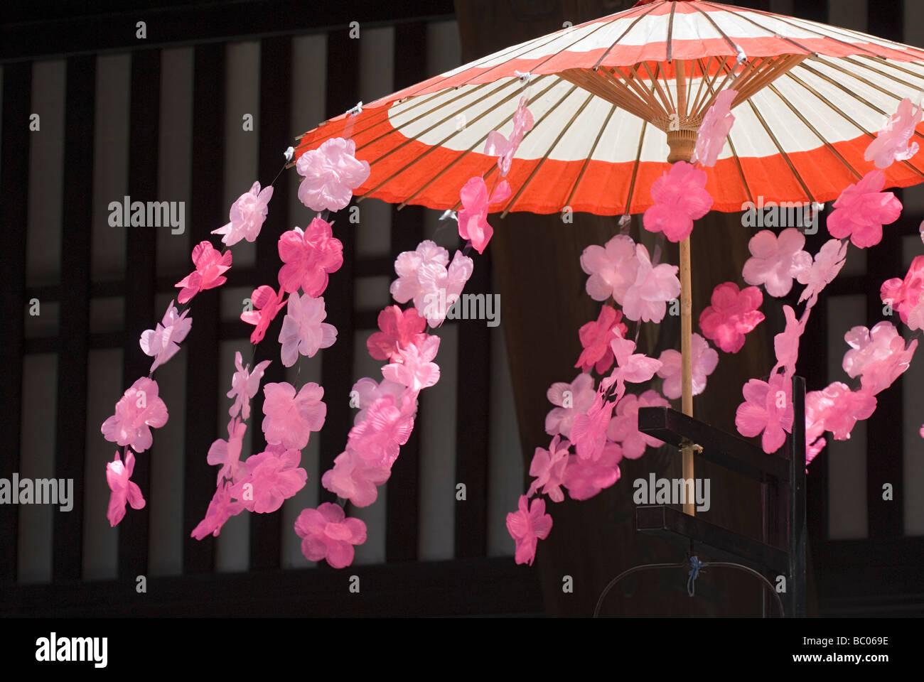 Wind weht Kunststoff Kirschblüten Blumen, die einen traditionellen Schirm während des Frühlingsfestes Stockbild