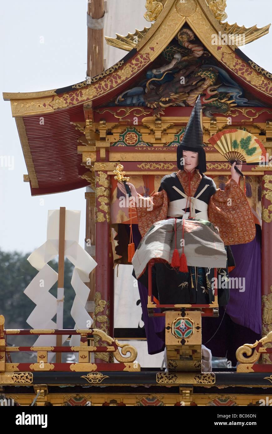 Einer mechanischen Marionette oder Puppe sitzt auf einer verzierten traditionelle hölzerne Schwimmer während Stockbild