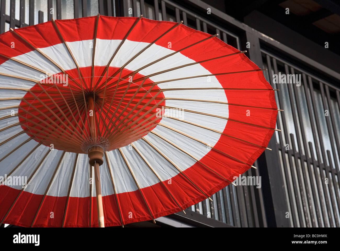 Ein weißer und roter traditionellen Regenschirm verleiht ein bisschen fröhlich Farbe einer traditionellen Stockbild