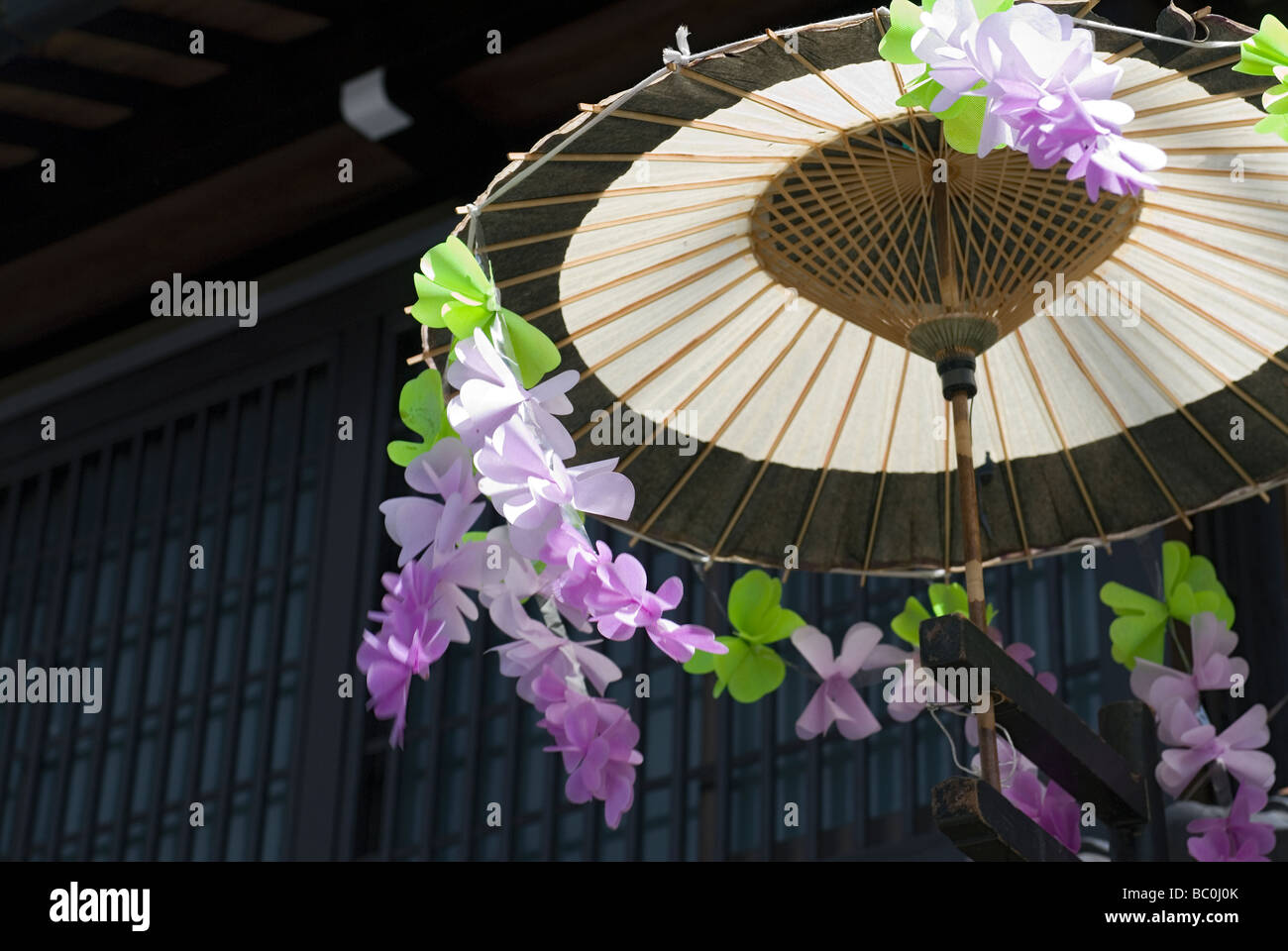 Wind weht Plastikblumen, die einen traditionellen Schirm während des Frühlingsfestes in Takayama schmücken Stockbild