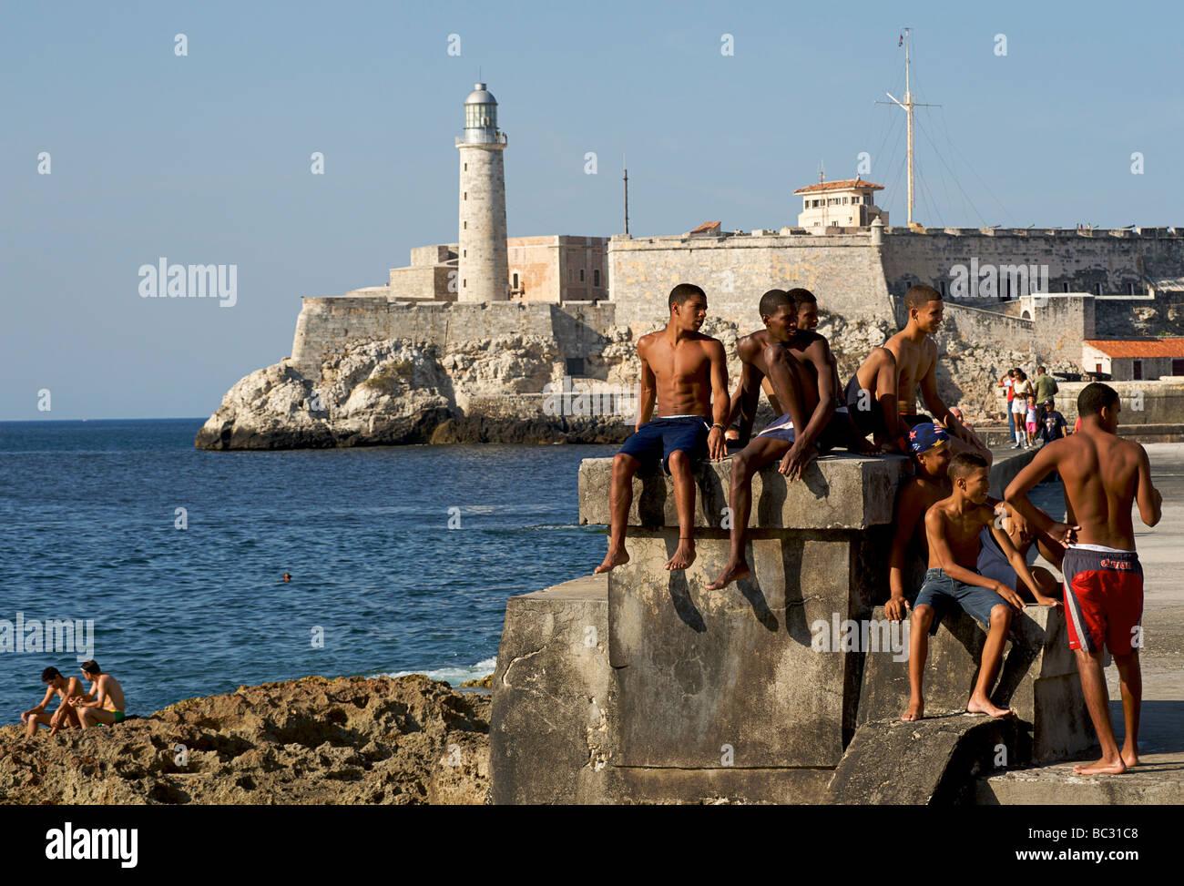 Kubaner genießen die Sonne und das Meer von den Felsen neben dem Malecon, Havanna, Kuba Stockbild