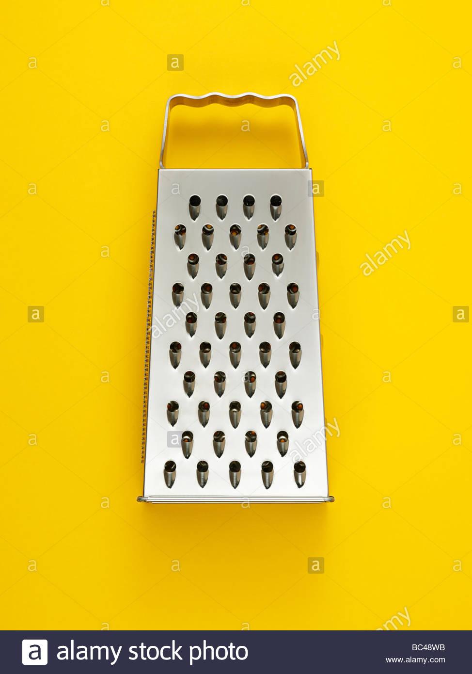 eine Käsereibe fotografiert auf einem gelben Hintergrund overhead Stockbild