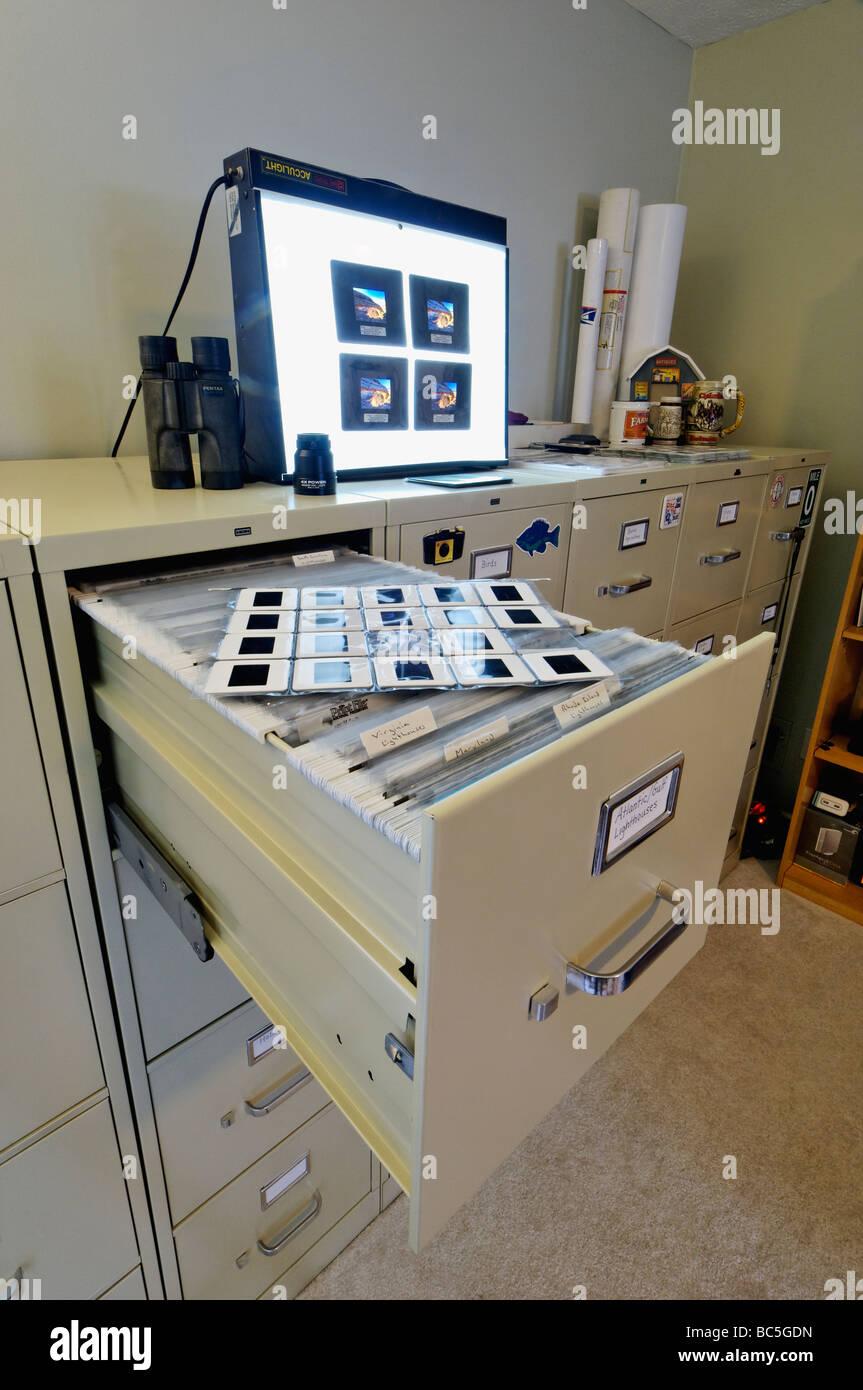 Aktenschränke schieben Foto Seiten Lichtkasten und Lupe im Fotografen-Büro Stockbild