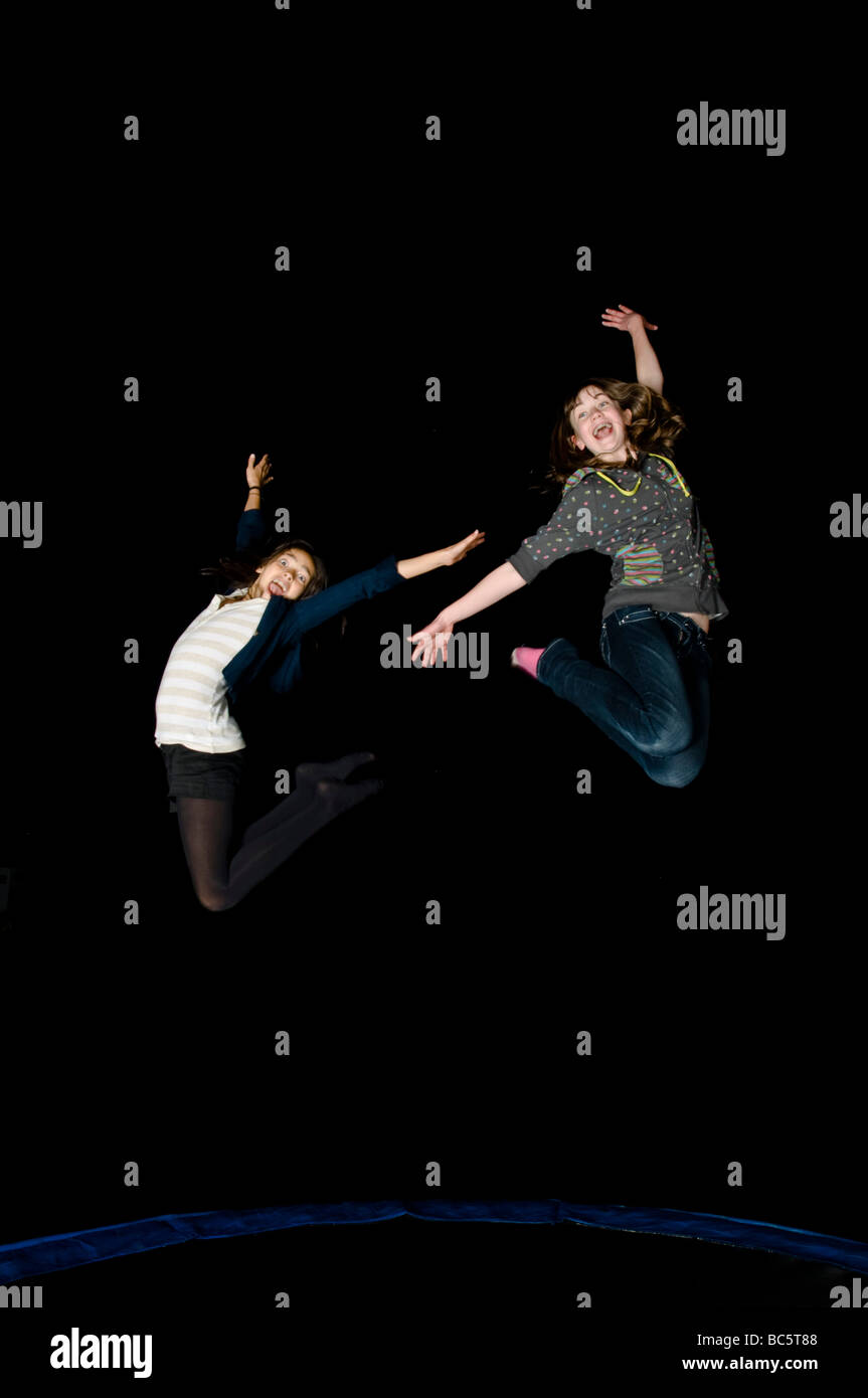 """2 junge Teenager-Freundinnen springen auf einem Trampolin beim Lachen in der Nacht auf einem Geburtstag """"Sleepover"""". Stockfoto"""