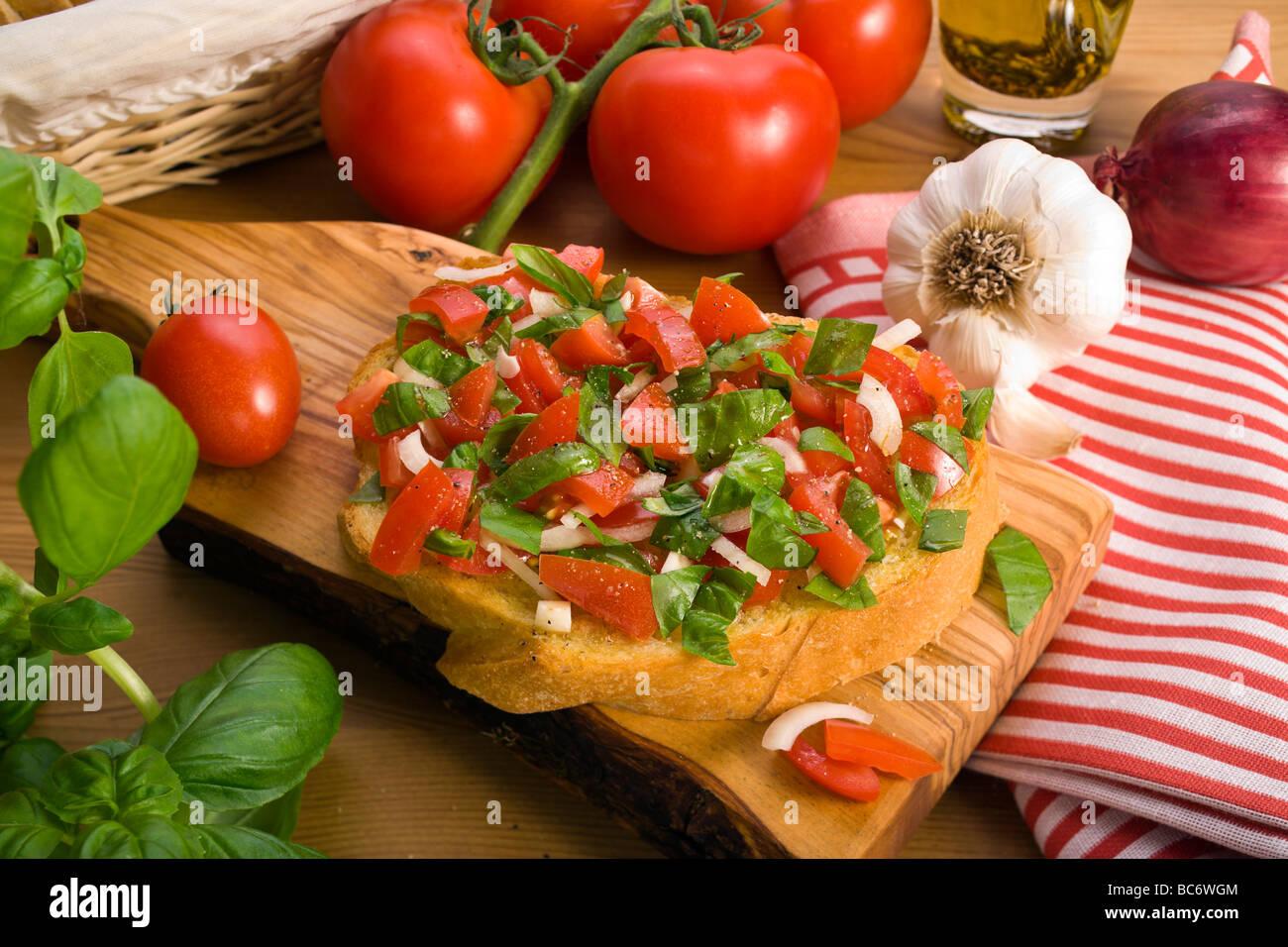 italienische Bruschetta-Brot serviert auf Oliven Holzbohle, verziert mit verschiedenen Zutaten Stockbild