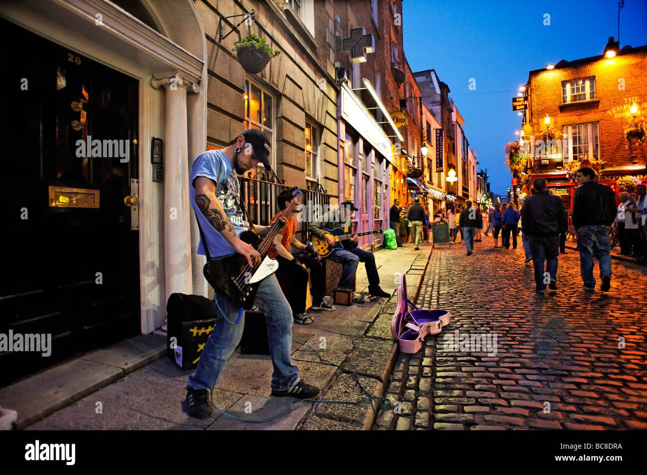Band als Straßenmusikant auf gepflasterten Straße von Temple Bar Nachtleben Dublin Irland Stockbild