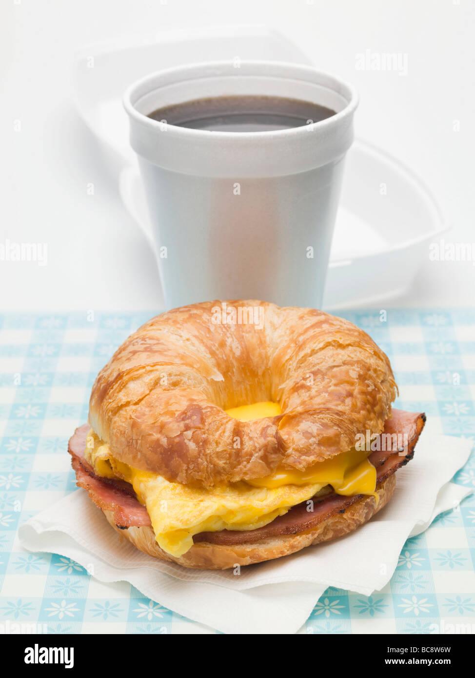 Croissant mit Rührei, Käse & Speck, Kaffee- Stockbild