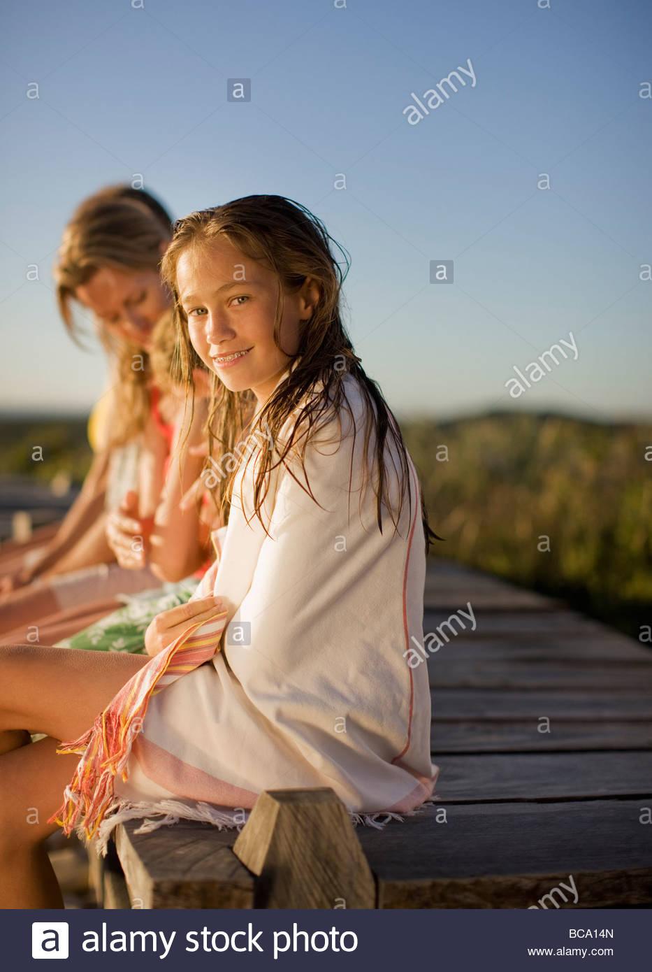 Familie sitzt am pier Stockbild