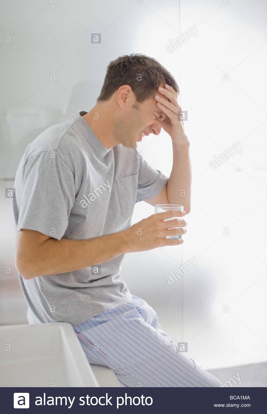 Mann mit Kopfschmerzen Trinkwasser Stockbild