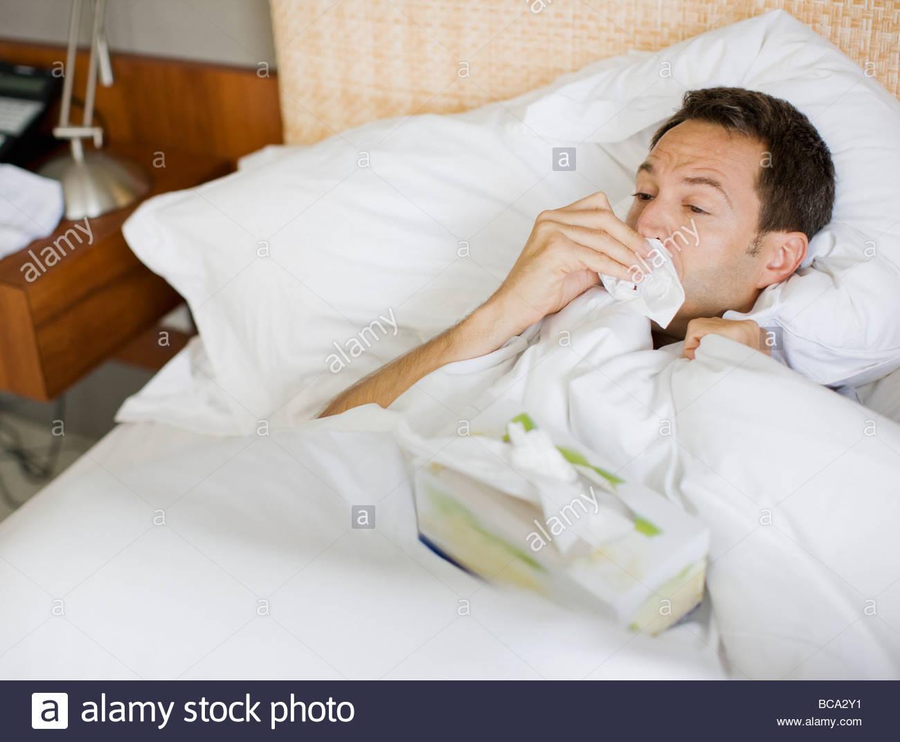 Mann krank im Bett abwischen Nase mit Gewebe Stockbild