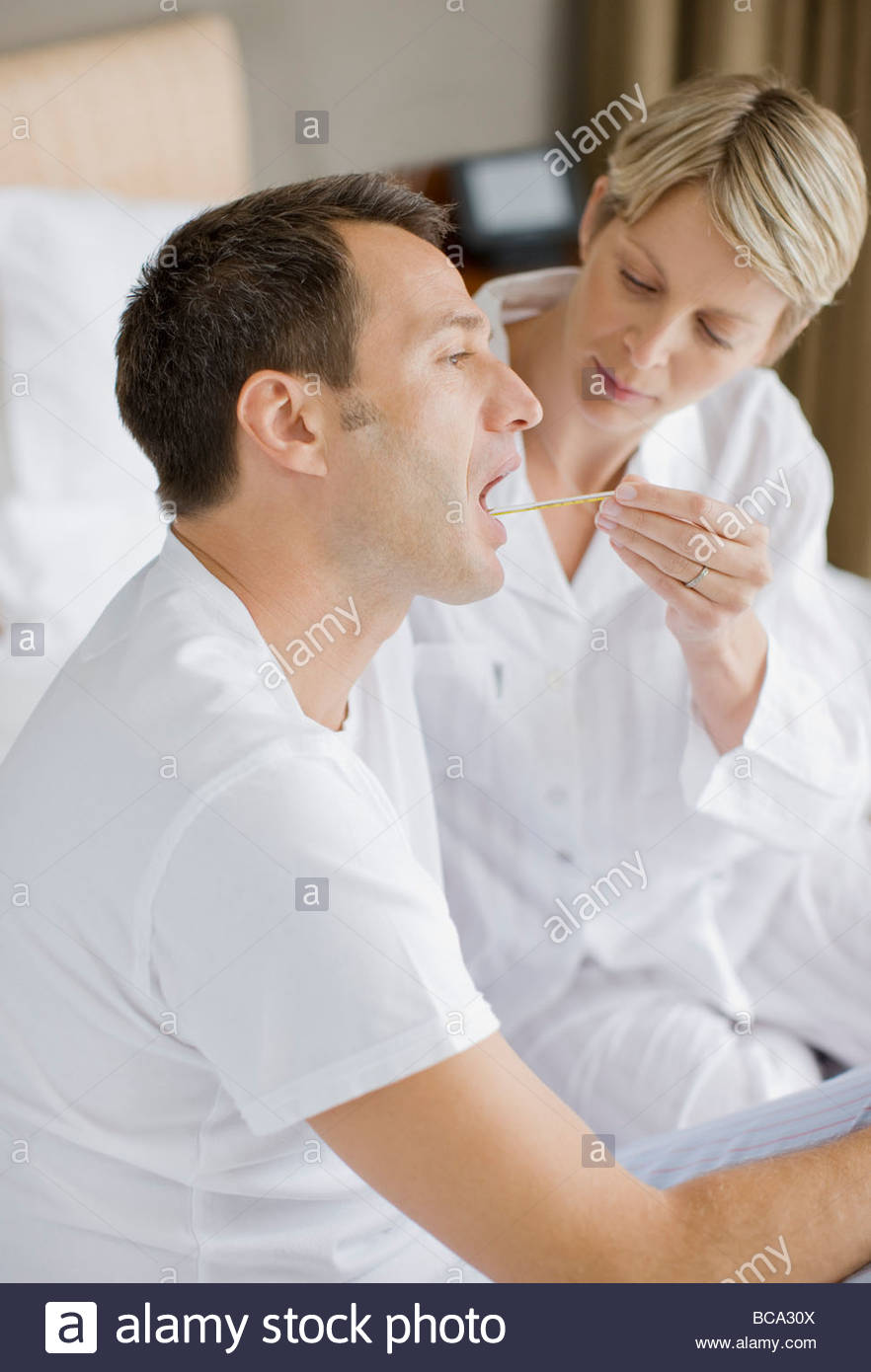 Frau nehmen Mannes Temperatur Stockbild