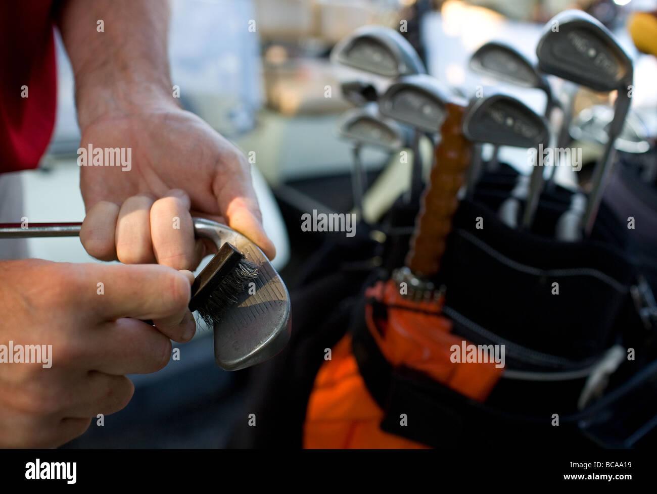 Ein Mann mit einem Pinsel um zu reinigen seine Golfschläger vor eine Runde Golf. Stockbild