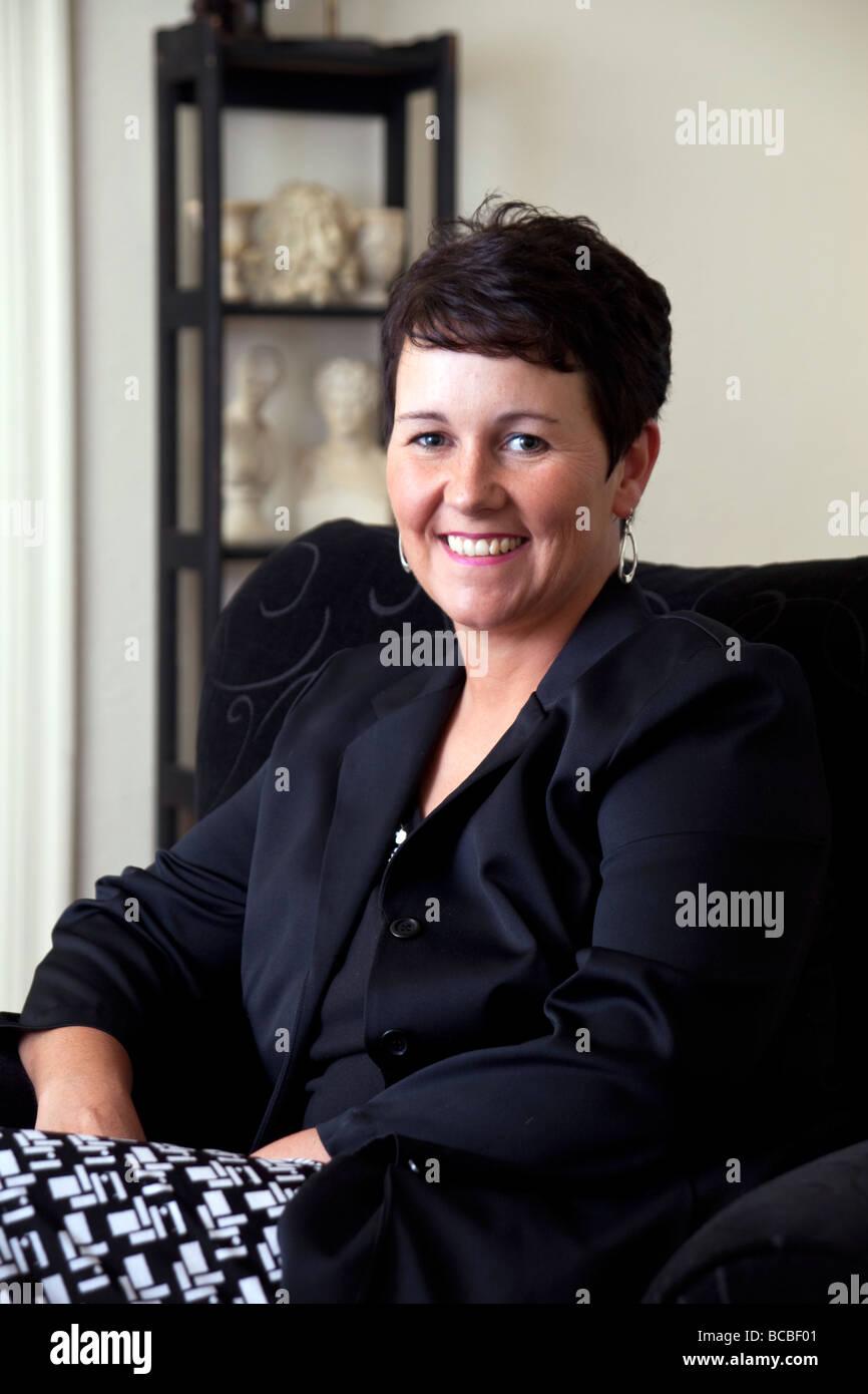 Schönen Lächeln auf den Lippen Business-Frau in ihren Dreißigern mit einem lässigen Hintergrund Stockbild