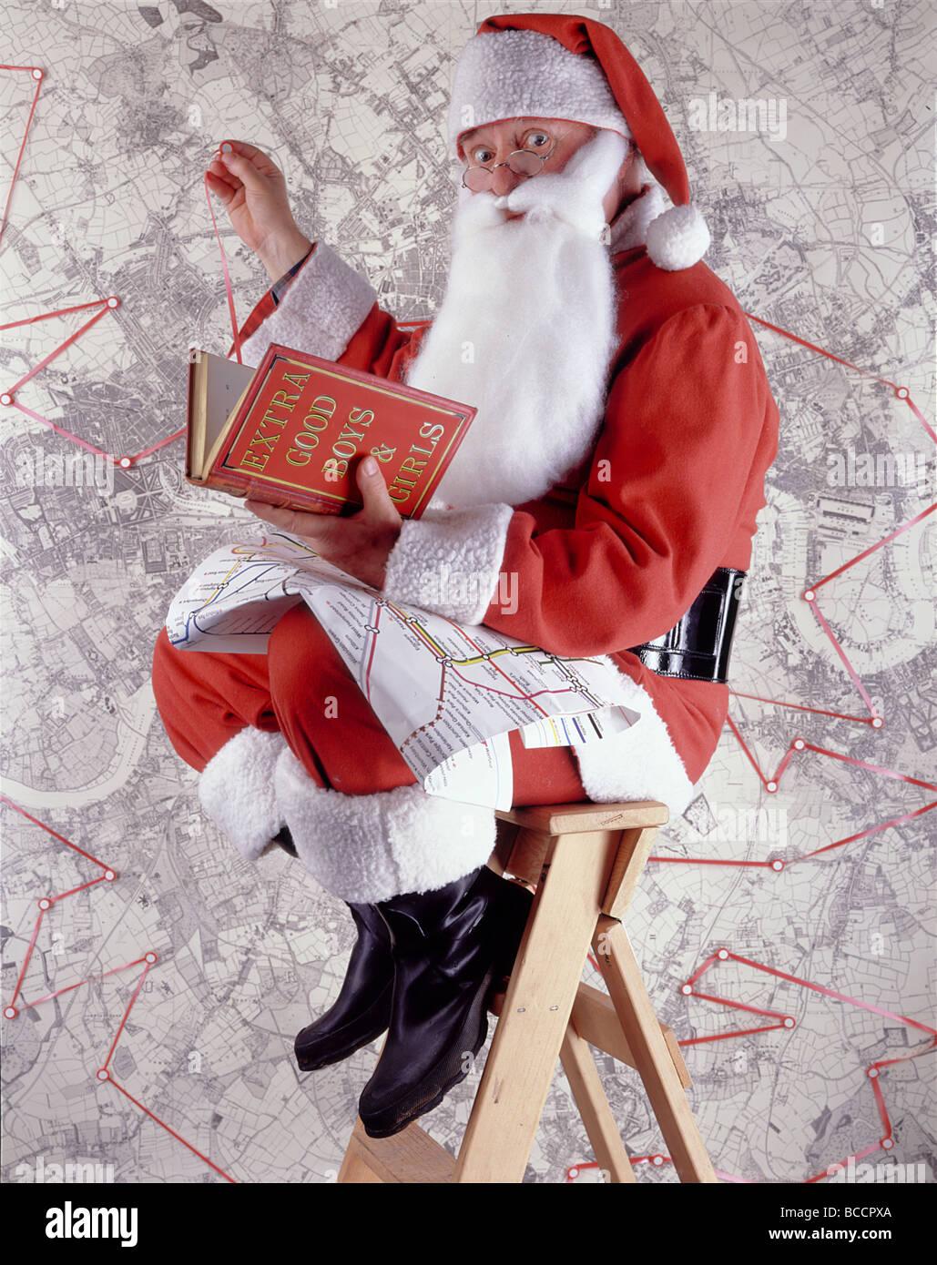 """Santa Claus (oder Weihnachtsmann) gegen Karte und Buch mit dem Titel """"EXTRA guten jungen & Mädchen"""" Stockbild"""