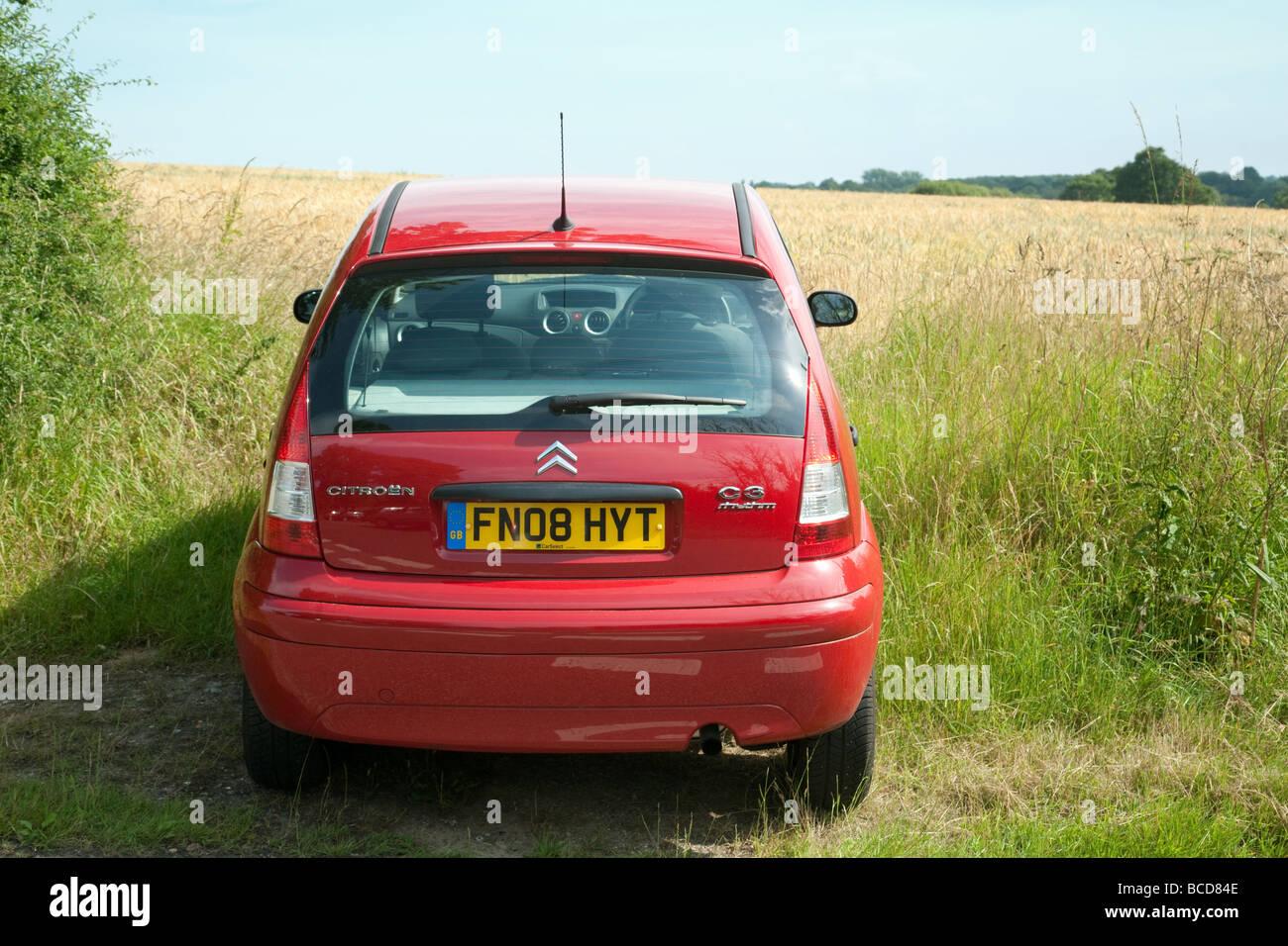 Ein rotes Auto geparkt am Rande eines Maisfeldes, Essex, England Stockbild