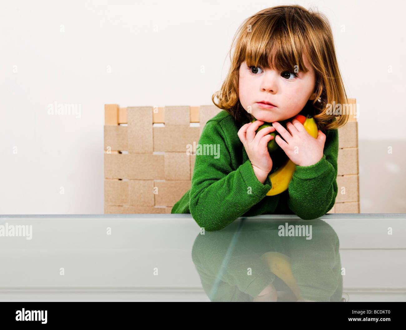 junges Mädchen mit Obst in Armen hält Stockbild