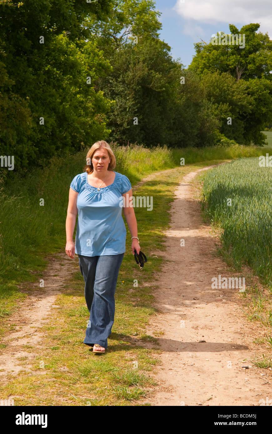 Eine Frau in ihren Dreißigern allein hinunter ein Land Feldweg in der britischen Landschaft im Frühling Stockbild