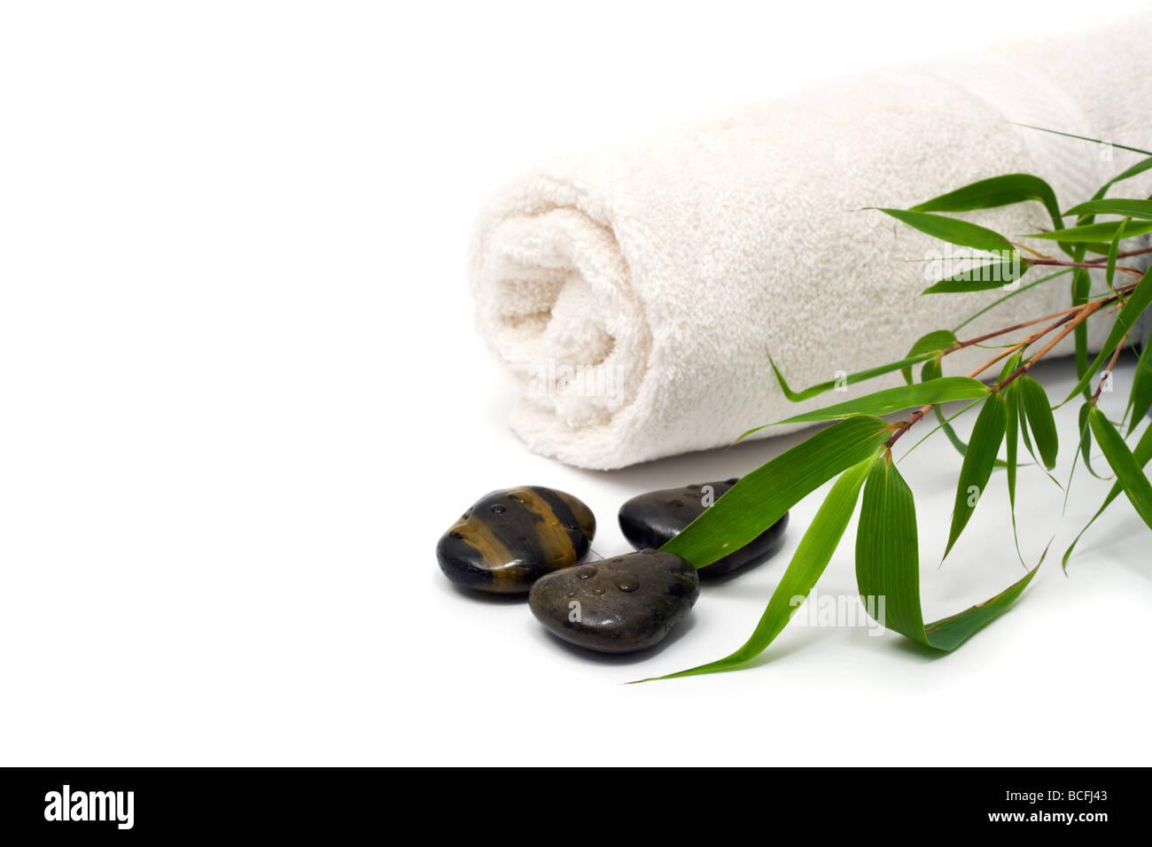 Wellness- und Spa-Konzept mit gerollten Handtuch, Kiesel, Bambus-Zweig, Ausschnitt Stockbild