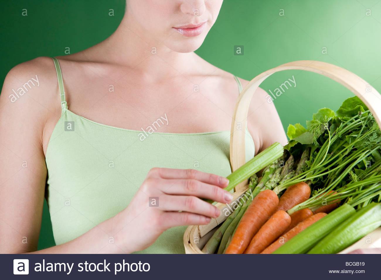 Eine junge Frau hält einen Korb voll mit Gemüse Stockbild