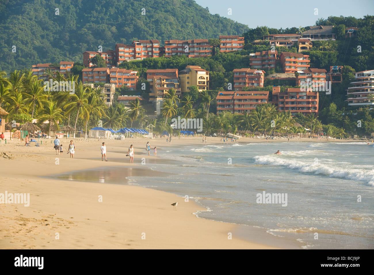 Ixtapa/Zihuatanejo Mexiko Menschen zu Fuß am Strand mit Hotels und Eigentumswohnungen im Hintergrund Stockbild