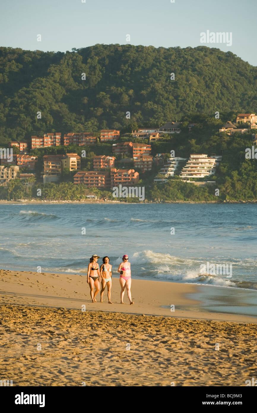 Ixtapa/Zihuatanejo Mexiko drei Weibchen zu Fuß am Strand mit Hotels und Eigentumswohnungen im Hintergrund Stockbild