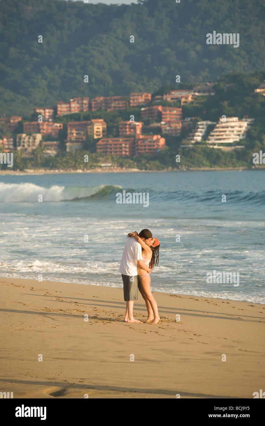 Ixtapa Mexico paar küssen im stehen am Strand mit Meer und Hotels Eigentumswohnungen im Hintergrund Stockbild