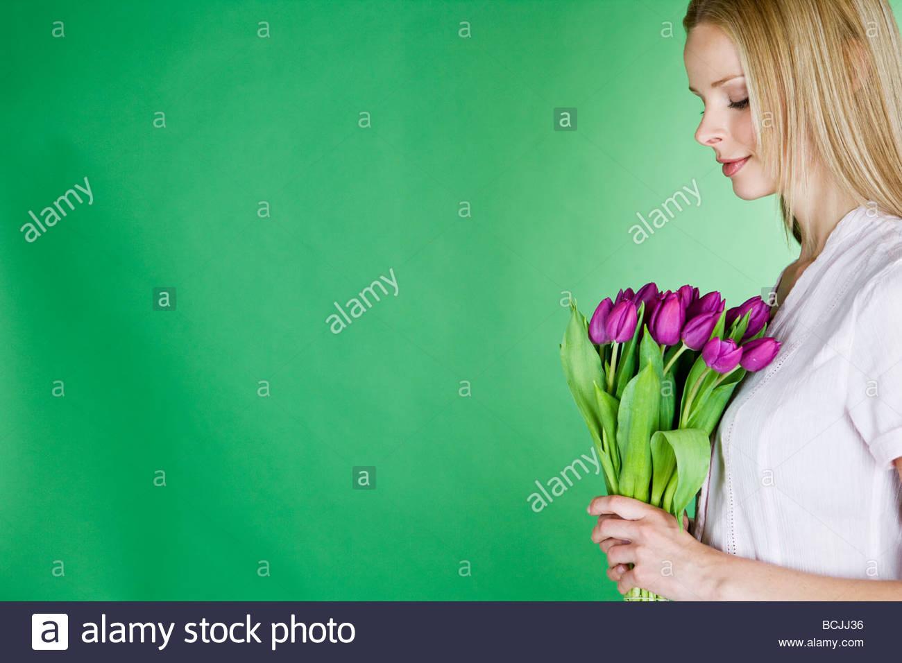 Eine junge blonde Frau hält eine Reihe von violette Tulpen im Profil Stockbild
