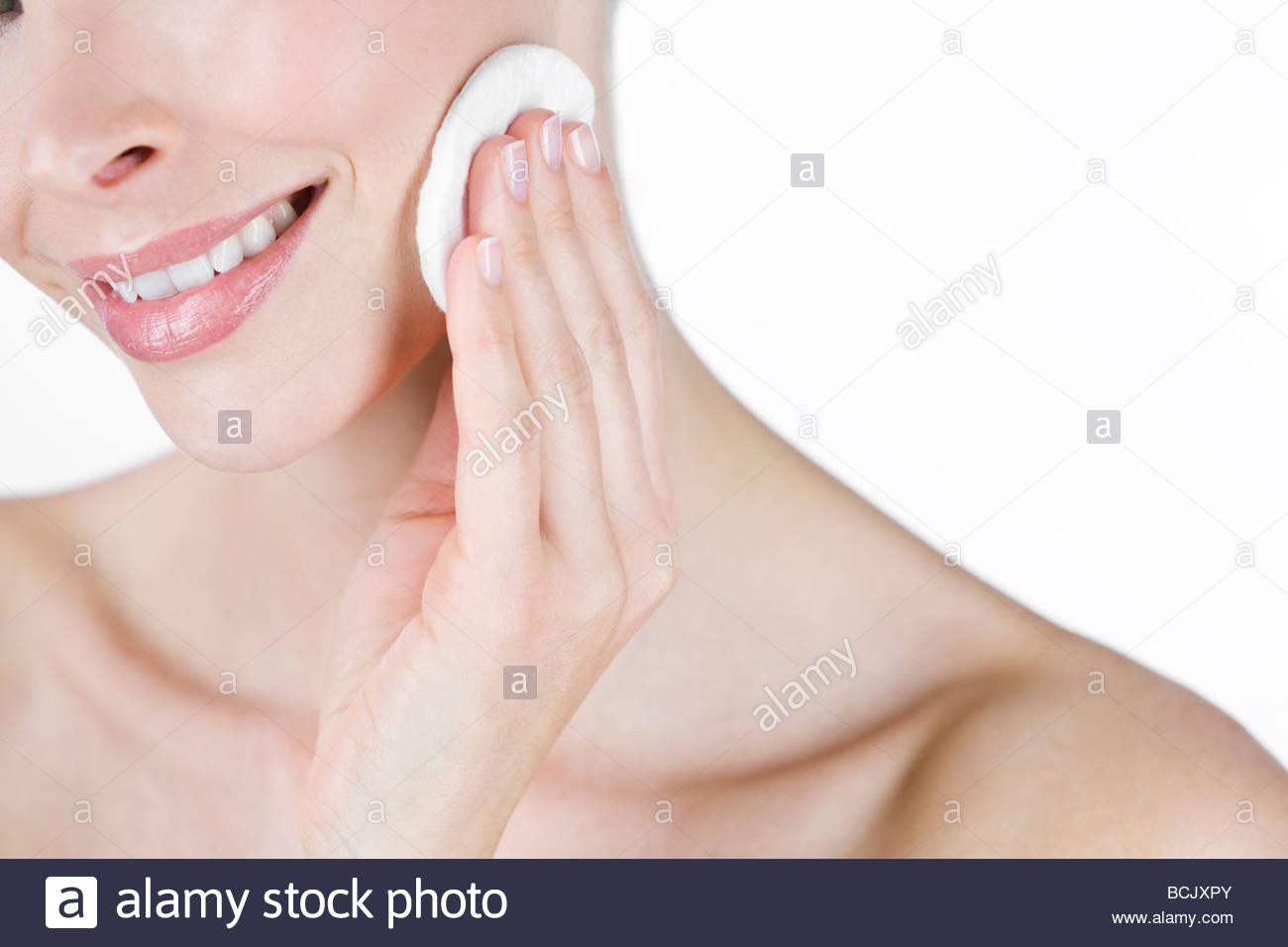 Ein Porträt einer jungen Frau, die ihr Gesicht reinigen Stockbild