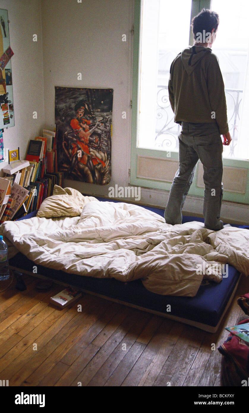 Junger Mann Im Schlafzimmer, Blick Aus Fenster, Sicht Nach Hinten Stockbild
